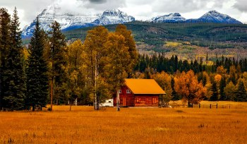 Meadow and cabin with Rocky Mountains in background