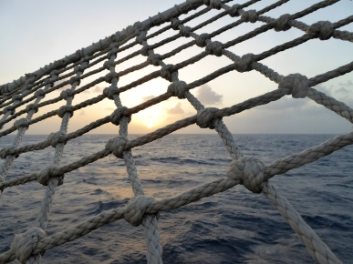 Laying in the bowsprit net watching the sun go down.
