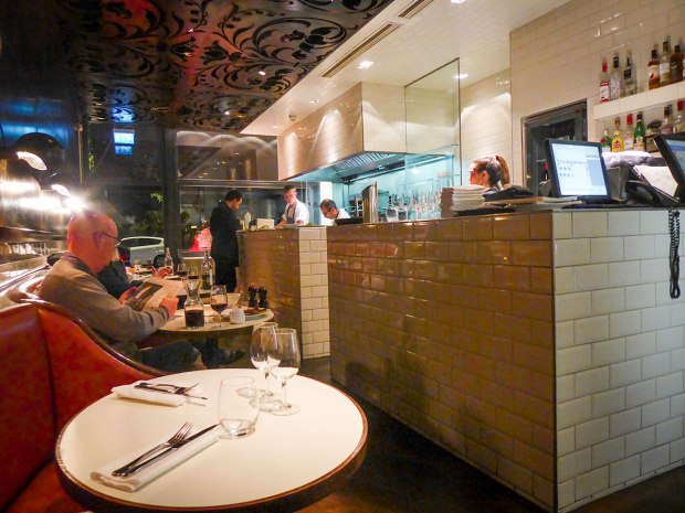 The front part of Hereford Road Restaurant in Notting Hill has cozy leather booths facing the open kitchen.