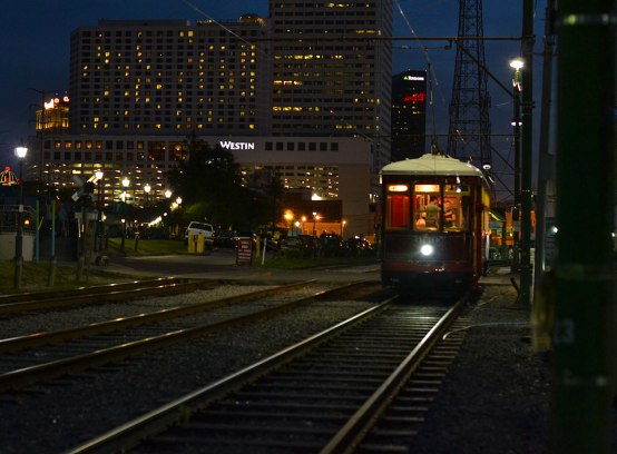 Streetcar along the river at twilight.