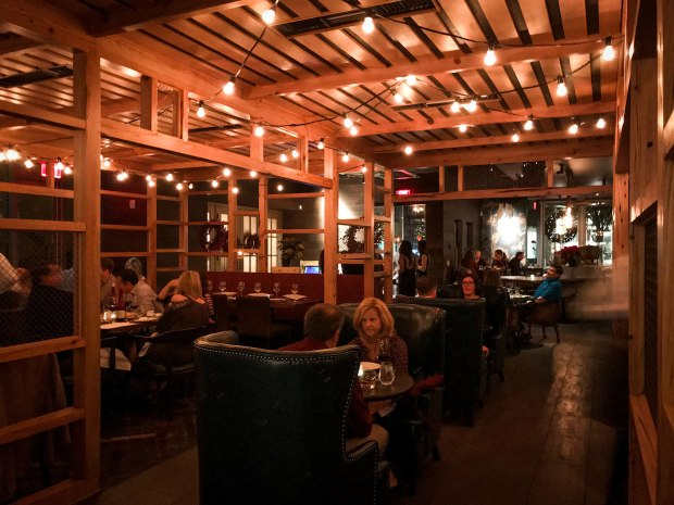 The central section of Fixe restaurant in Austin makes you feel like you're sitting outside on a screened porch.