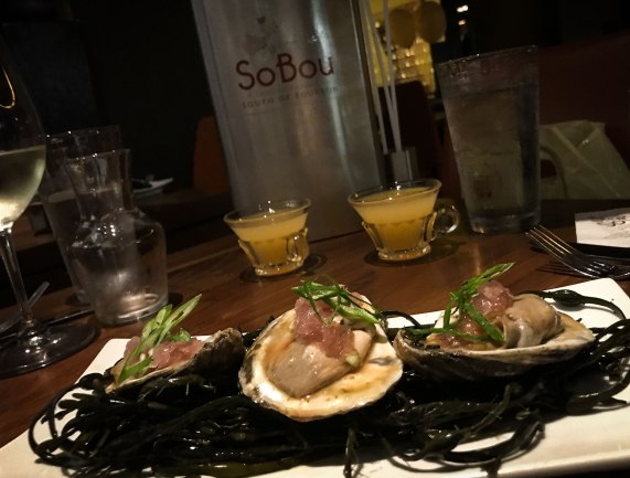 Smoky oysters en escabeche -- with a bottle of hooch in the background at SoBou restaurant in New Orleans